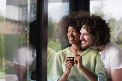 Happy multiethnic couple relaxing at modern home indoors Stock Image