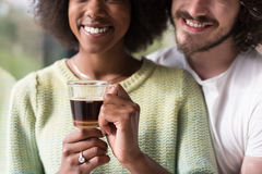 Happy multiethnic couple relaxing at modern home indoors Stock Photography