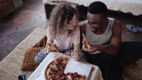 Happy multiethnic couple sitting on the flow, hugging and eating fast food. Woman feed the hungry man a slice of pizza. Stock Images