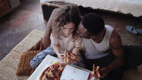 Happy multiethnic couple sitting on the flow, hugging and eating fast food. Woman feed the hungry man a slice of pizza. Royalty Free Stock Images