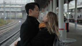 The happy multiethnic couple stands in the train station, talks and hugs enjoying their meeting. The asian man wears dark coat and his girlfriend has round stock video