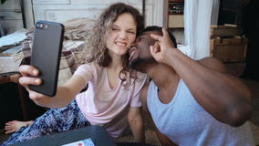 Happy multiethnic couple taking selfie photos on smartphone. Woman and man in pajamas make funny looking face, have fun. stock video footage