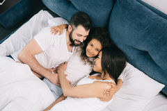 Happy multiethnic family hugging while lying together in bed royalty free stock images