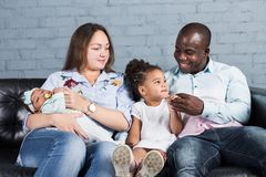 Happy multiethnic family sitting on the sofa in modern interior stock photography