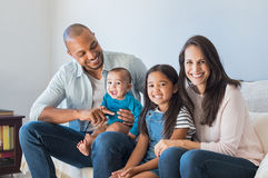 Happy multiethnic family on sofa. Portrait of happy multiethnic family sitting on sofa at home. Smiling couple with kids sitting on couch and looking at camera