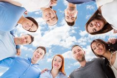 Happy multiethnic friends forming huddle against sky Royalty Free Stock Image