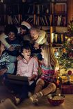 Multiethnic friends watching movie together on laptop on Christmas eve. Happy multiethnic friends watching movie together on laptop on Christmas eve royalty free stock image