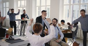 Happy multiethnic fun business people celebrating success together with excited male boss riding office chair clapping. stock video