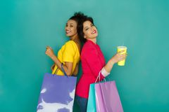 Excited multiethnic girls with shopping bags and coffee cup Stock Photography