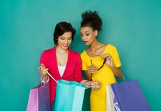 Excited smiling multiethnic girls with shopping bags royalty free stock image