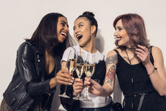 Happy multiethnic girls drinking champagne at party. Young happy multiethnic girls drinking champagne at party Stock Photography