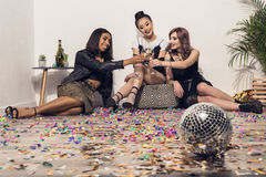 Happy multiethnic girls sitting and drinking champagne at party royalty free stock photos