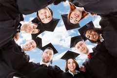 Happy multiethnic graduates forming huddle against sky. Directly below portrait of happy multiethnic graduates forming huddle against sky Royalty Free Stock Photos