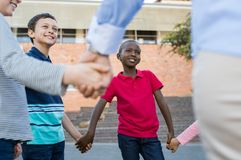 Group of children holding hands. Happy multiethnic kids holding hands together outside the school. Group of happy children smiling and listening to game rules stock photography