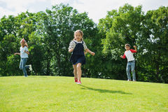 Happy multiethnic kids playing and running together on green grass in park. Adorable happy multiethnic kids playing and running together on green grass in park Stock Photos