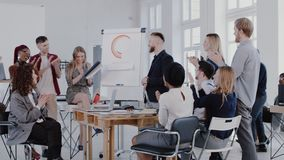 Happy multiethnic managers team clapping to middle aged CEO businessman at modern office meeting, slow motion RED EPIC. Diverse start-up partners applause to stock video footage