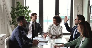 Happy multiethnic professional business team give high five in office