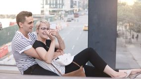 Happy multiethnic romantic couple sitting on a New York street bridge, taking smartphone selfie and having fun smiling. Cheerful relaxed newlyweds post stock video