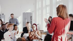 Happy multiethnic team applause to female coach leading conference seminar at modern trendy office slow motion red epic.