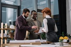 Happy multiethnic team of architects discussing documets. At office stock photo