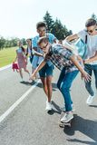 happy multiethnic teenage classmates having fun with skateboard and walking together stock photography