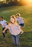 Multiethnic teens running in park. Happy multiethnic teens running together in park Royalty Free Stock Photos