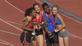 Happy multiethnic winners posing to cameras on sport field, successful team