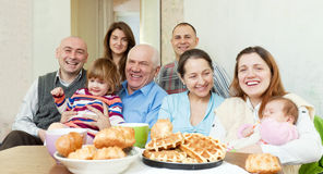 Happy multigeneration family communicate around tea. Portrait of happy multigeneration family communicate around tea table at home Stock Photo