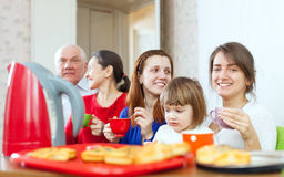 Happy multigeneration family communicate over tea. With cakes Stock Images