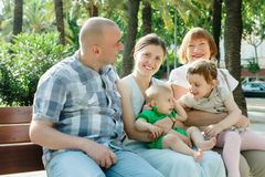 Happy multigeneration family of five. Sitting on bench in sunny summer day Stock Photos