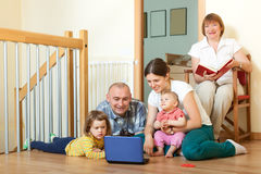 Happy multigeneration family together with blue laptop at home. Happy multigeneration family together laptop at home on the floor Stock Image
