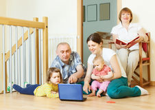 Happy multigeneration family together with notebook Royalty Free Stock Photo