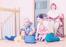 Happy multigeneration family together with notebook. At floor at home Royalty Free Stock Photo