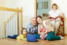 Happy multigeneration family with two children. With laptop on floor at home Royalty Free Stock Photo