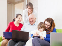 Happy multigeneration family uses few portable electronic commun Stock Photography