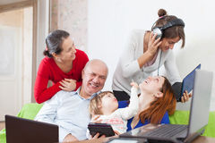 Happy multigeneration family uses electronic devices. Happy multigeneration family uses few various electronic devices at home interior Stock Image