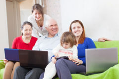 Family uses few various portable devices in home interior Stock Photo