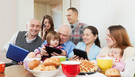 Happy multigeneration family using devices. Portrait o Happy multigeneration family using electronic devices over tea  in home Stock Photography
