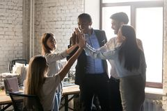 Happy multinational coworkers giving high five celebrating great teamwork result stock photography