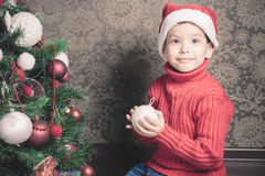Happy multiraceal boy decorating a christmas tree Royalty Free Stock Images