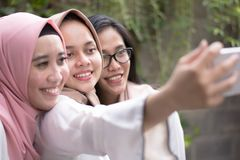 Group happy young muslim taking selfie together royalty free stock photos