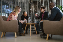 Happy multiracial business people in meeting. Multiracial business team sitting in office lobby discussing new business ideas. Young men drinking water. Happy Royalty Free Stock Image