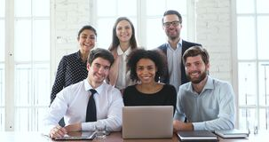 Happy multiracial business team show thumbs up recommend corporate software