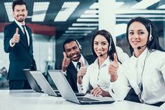 Happy multiracial call center team shows thumbs up stock photo