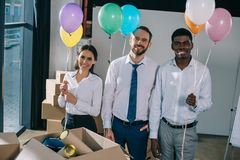 Happy multiracial colleagues holding colorful balloons and smiling at camera in new. Office royalty free stock photos