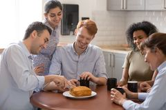 Happy diverse colleagues cut cake celebrating in office kitchen stock image