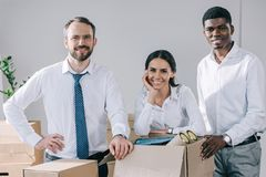 Happy multiracial colleagues smiling at camera and unpacking boxes in new office royalty free stock photo
