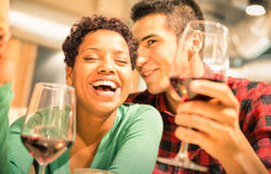 Happy multiracial couple drinking red wine at fashion bar Royalty Free Stock Photography
