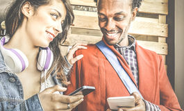 Happy multiracial couple flirting and dating with smartphone numbers. Multiracial couple flirting with smartphone numbers - Modern concept of mobile phone stock images