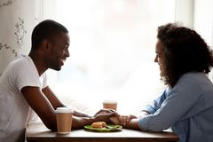 Happy multiracial couple holding hands, enjoying date in cafe royalty free stock image
